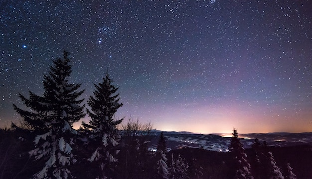 Magical view of the starry clear sky spread over the night ski resort in cloudless cold weather in winter.