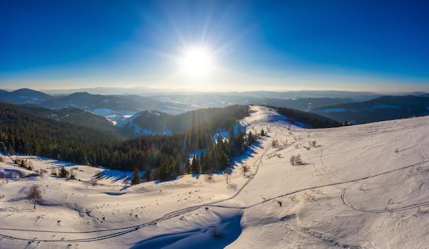 晴れた、風のない凍るような日にヨーロッパのスキーリゾートで美しい雪の斜面の魔法の冬のパノラマ。冬のアクティブなレクリエーションの概念 Premium写真