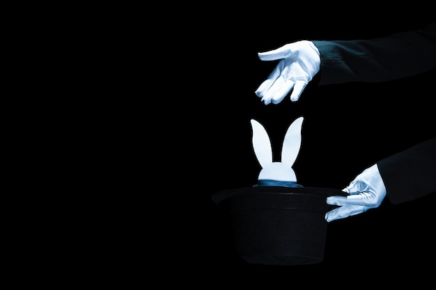 Magician holding black top hat with white rabbit head against black background