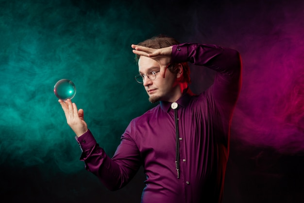 The magician makes a levitation show of the glass sphere.