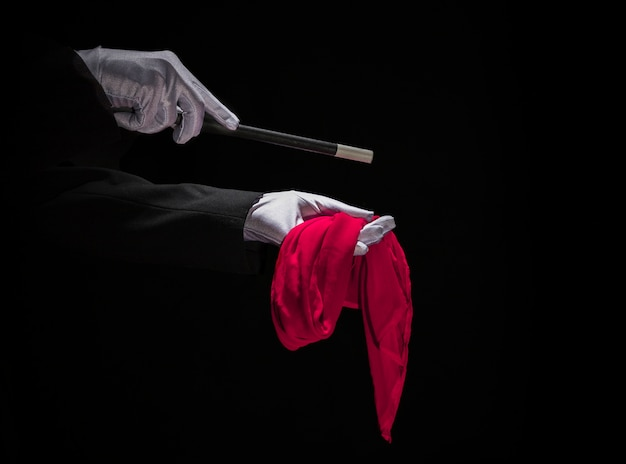 Magician performing trick on red napkin with magic wand against black background