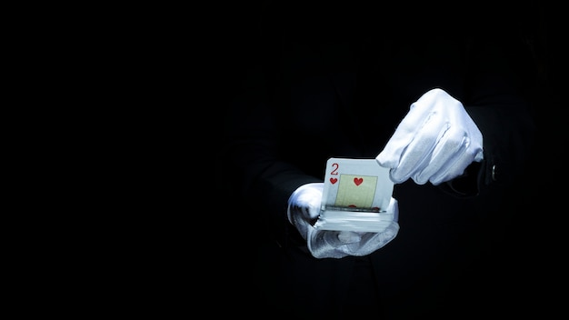 Magician performing trick with playing cards against black background