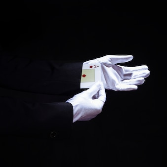 Magician removing aces playing card from the hand against black background