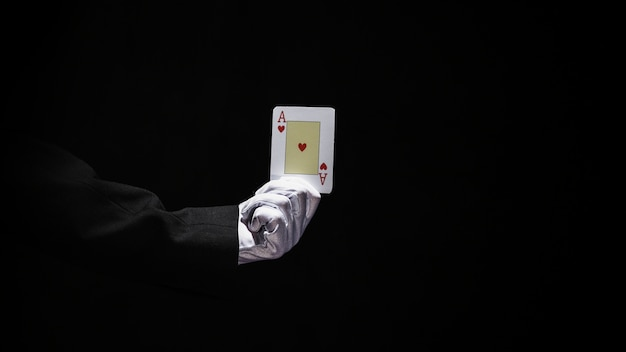 Magician's hand holding aces playing card against black background