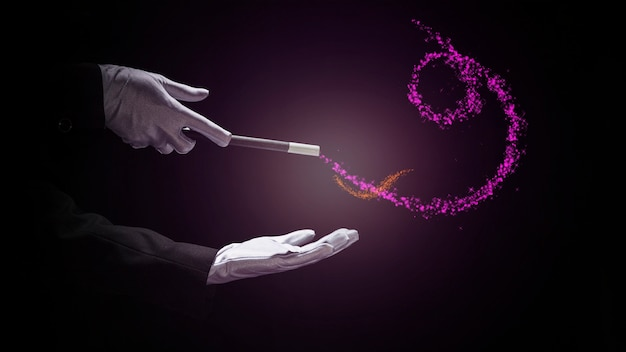 Magician's hand performing trick with magic wand against black background
