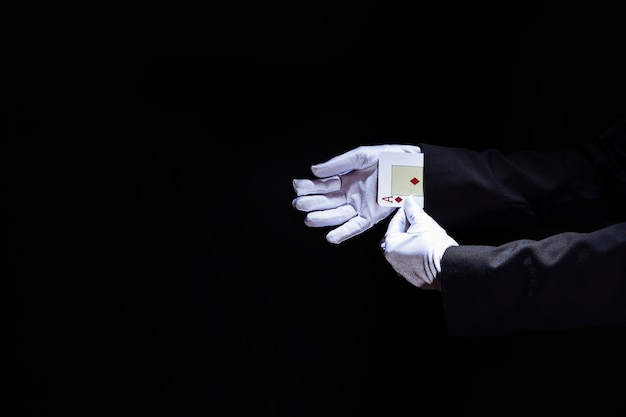 Magician's hand removing aces playing card from the sleeve against black background