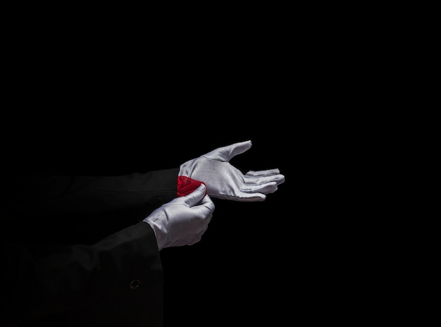 Magician's hand removing red napkin from the sleeve against black background