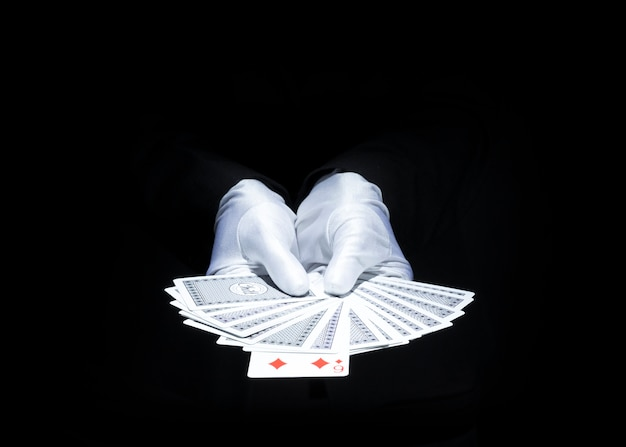 Magician's hand showing fanned deck of playing card against black background