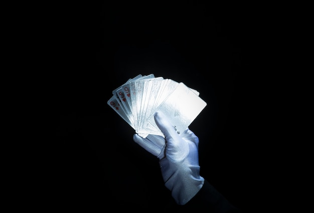 Magician's hand wearing white glove holding fanned playing cards against black background