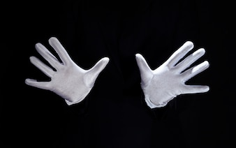 Magician's hand wearing white gloves against black background