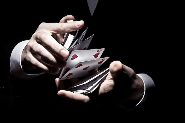스포트라이트 아래 멋진 방식으로 카드를 섞는 마술사