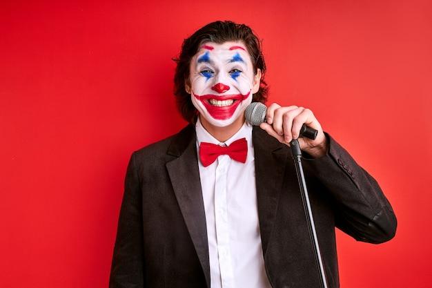 赤い背景に分離されたマイクを持つマジシャン、うれしそうな魔法のトリックの男または黒いスーツの謎の男が話し、笑顔