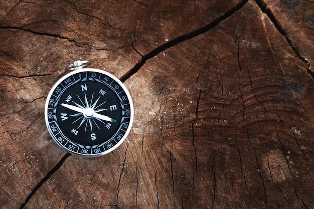 グローバル旅行の木製の背景の概念の磁気コンパス