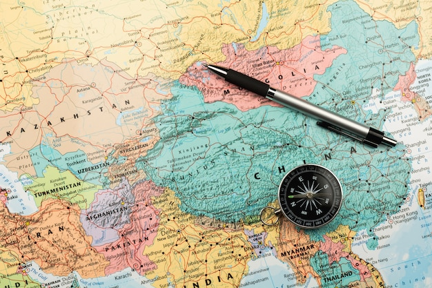 Magnetic compass and a pen on map.