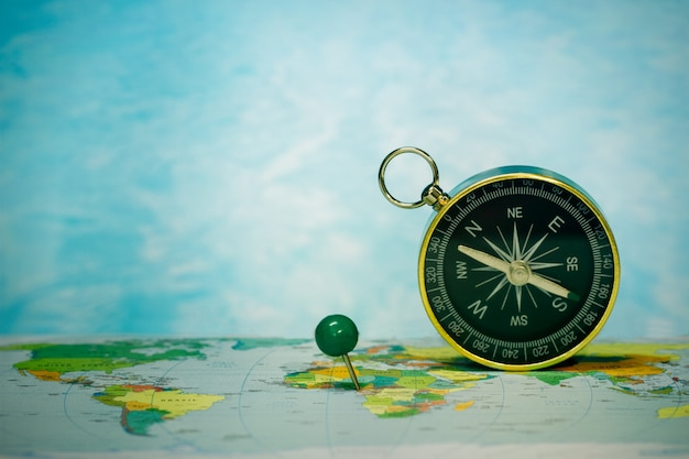 Magnetic compass on world map, concept of travel and destination, macro travel