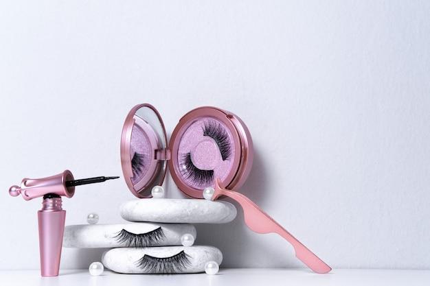 Магнитные накладные искусственные ресницы в розовом зеркальном комплекте, подводка для глаз, пинцет на белом фоне. домашнее наращивание ресниц, концепция косметологического инструмента, косметический уход, улучшение внешнего вида