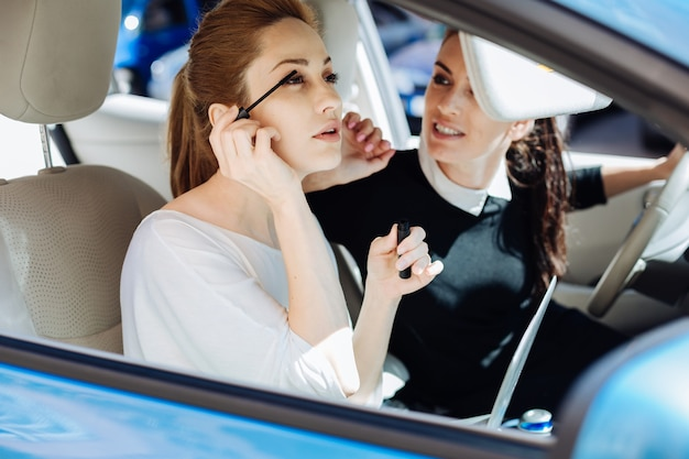 Магнитный вид. красивая милая привлекательная бизнесвумен использует тушь и красит ресницы, сидя в машине