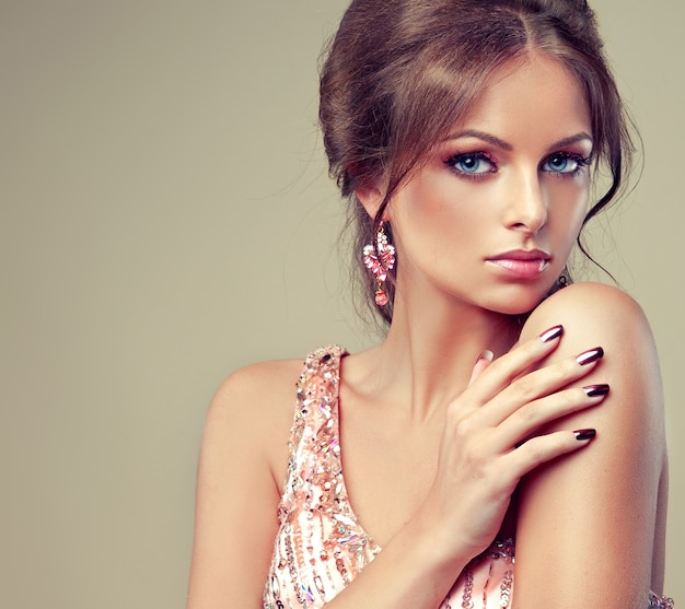 아름다운 파란 눈의 마그네틱 모양. 도금 매니큐어로 날씬한 손가락은 밝은 저녁 화장과 반짝이는 가운을 입은 젊은 여성의 매력적인 얼굴을 만지고 있습니다. 우아함과 스타일.