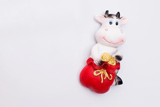 白い冷蔵庫の上の雄牛の形の磁気おもちゃ。幸運をもたらすお金のある雄牛の形の磁石