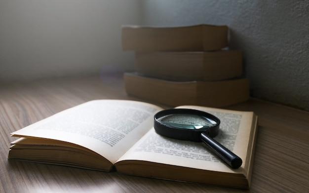 暗い部屋の開いた本の上にある拡大鏡