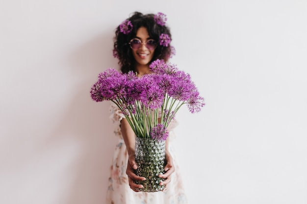 Magnificent african lady holding vase of purple flowers. indoor portrait of romantic black young woman having fun at home in weekend.