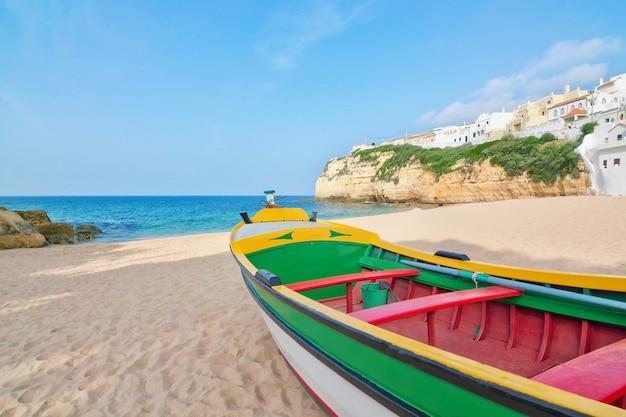 Великолепный пляж на побережье португалии у виллы карвоейру. рыбацкая лодка на переднем плане.
