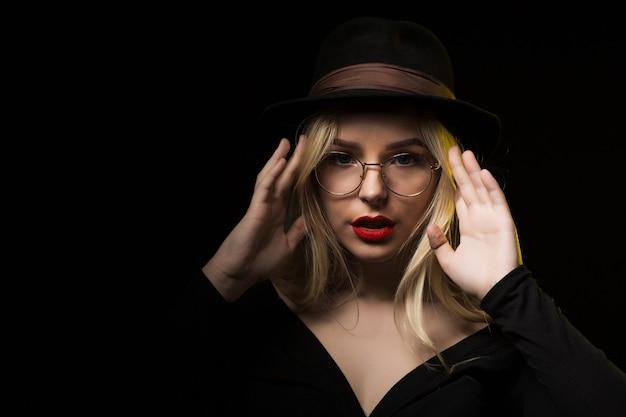 黒のブラウス、帽子、眼鏡を身に着けて、影でポーズをとる壮大なブロンドの女性