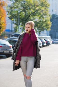 코트와 청바지를 입고 주차장에서 부드러운 백라이트와 함께 포즈를 취하는 장엄한 금발의 여자