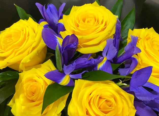 アイリスの花と黄色いバラの壮大な花束。閉じる