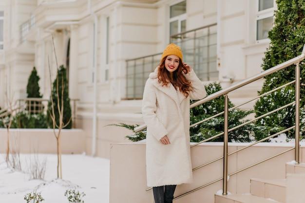Magnifica ragazza caucasica trascorrere il fine settimana invernale all'aperto. piacevole donna allo zenzero in posa in camice bianco.