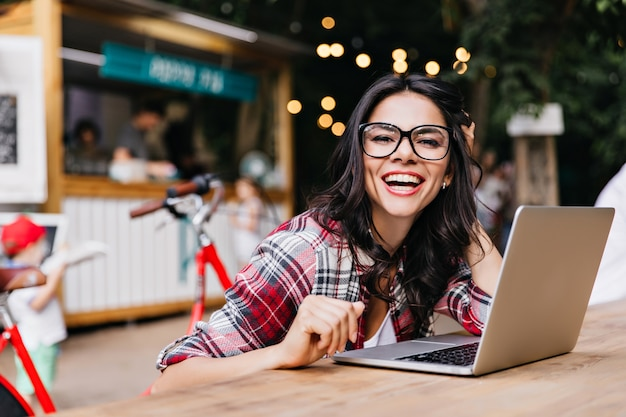 Magnificent caucasian woman in casual outfit posing with laptop. debonair latin female student laughing.
