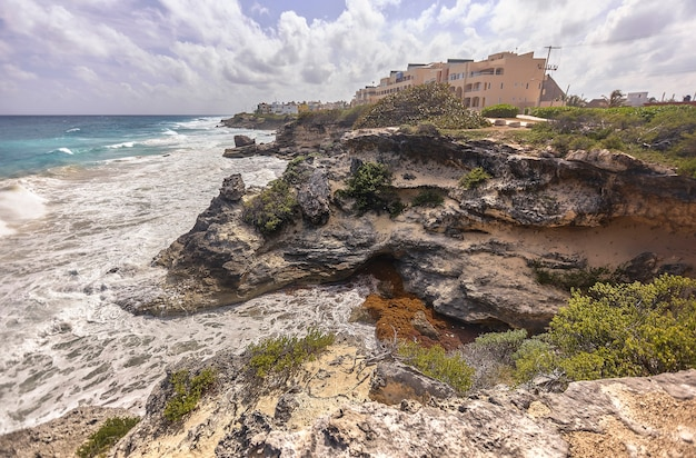 Великолепный обрыв на берегу моря, прямо над которым построены дома. панорама исла-мухерес в мексике