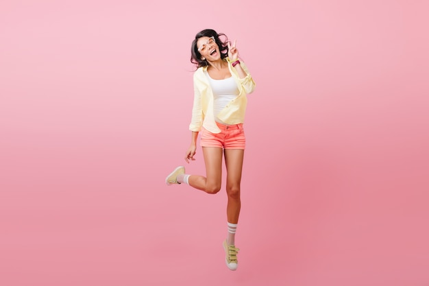 Magnificent dark-haired lady in trendy outfit standing on one leg for photo. indoor portrait of joyful latin young woman in stylish yellow shoes.