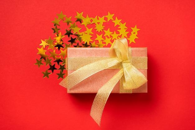 Великолепный праздничный подарок в золотой упаковке и чаша с золотой лентой на болтовню со звездами.