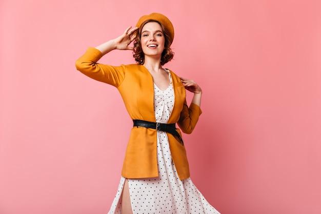 笑顔でカメラを見ている壮大なフランスの女の子。黄色いベレー帽の魅力的な若い女性のスタジオショット。