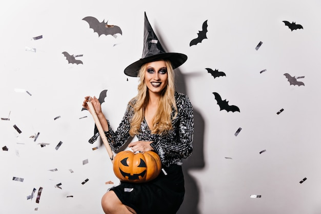 Великолепная девушка в блузке блеска держит тыкву хеллоуина. фотография в помещении улыбающейся довольной ведьмы в черной шляпе.