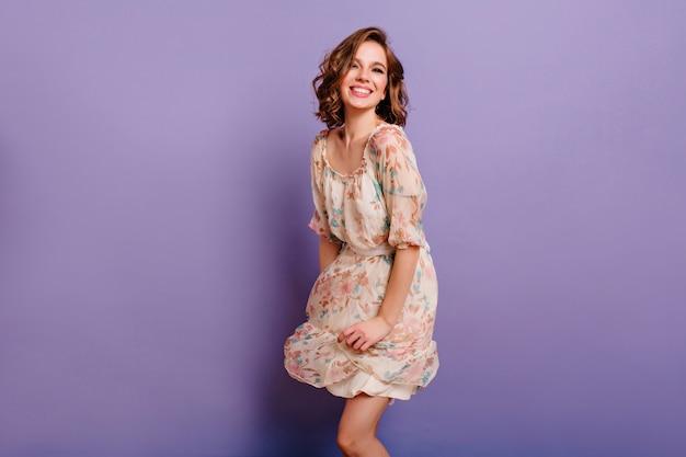Великолепная девушка со светло-каштановыми вьющимися волосами танцует с улыбкой в фиолетовой студии