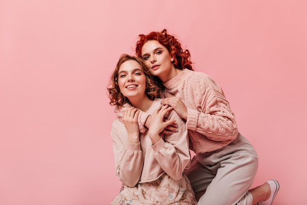 분홍색 배경에 포즈 유행 복장에 웅장 한 여자. 포용과 카메라를보고 두 친구의 스튜디오 샷.