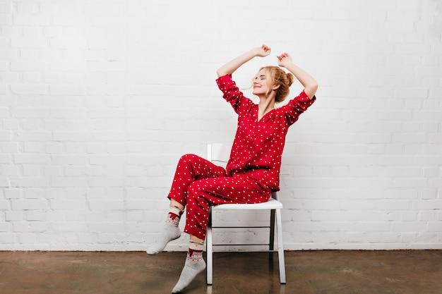 아침을 즐기는 아늑한 빨간 잠옷에 웅장한 아가씨. 흰색의 자에 앉아서 스트레칭 파자마에 웃는 유럽 소녀.