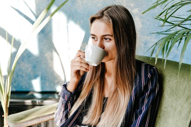 기쁨과 함께 커피를 마시는 장엄한 장발 소녀. 집에서 아침을 즐기는 매력적인 여성 모델.