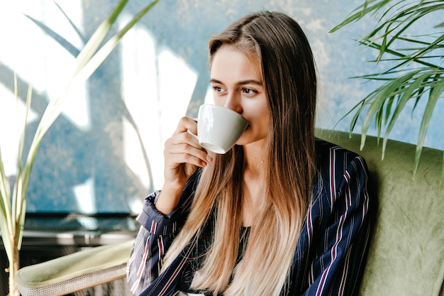 Magnificent long-haired girl drinking coffee with pleasure. appealing female model enjoying morning at home.
