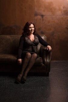 暗い部屋の革のソファでポーズをとってファッショナブルなアパレルで壮大な成熟したブルネットの女性