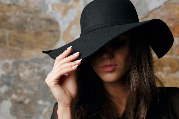 暗闇の中でポーズをとる彼女の目を覆う帽子をかぶった壮大なモデル。テキスト用のスペース