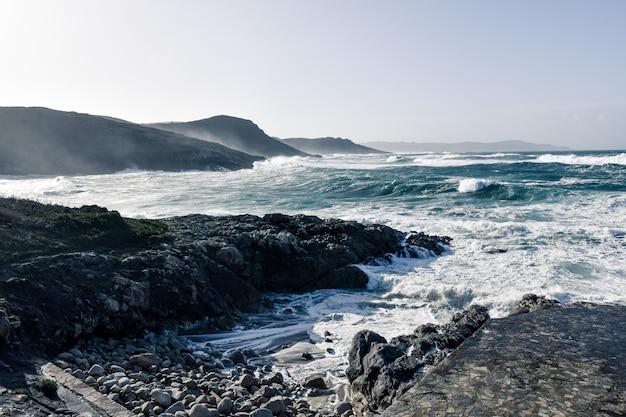 曇りの日にビーチの美しい岩にやってくる壮大な海の波