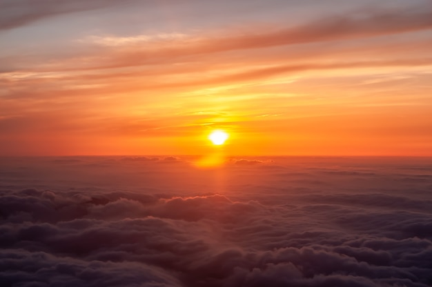 Magnificent orange sunset seen from airplane sea off fluffy clouds colorful sky