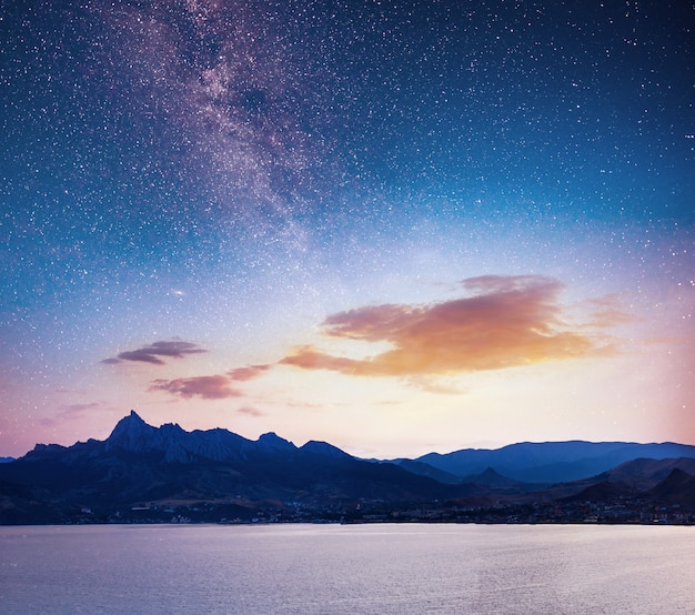 Magnificent panorama of sunrise over the sea. vibrant night sky with stars and nebula and galaxy. deep sky astrophoto