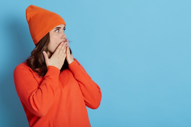 Magnificent pretty lovely gorgeous cheerful dark haired girl in casual orange sweater and cap, looking aside and coning mouth with palms