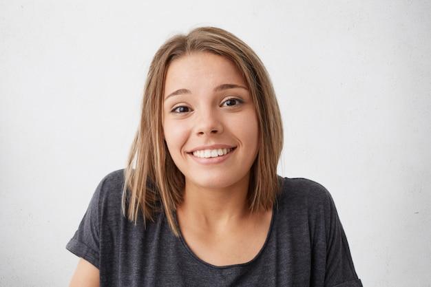 어둡고 좁은 눈과 멋지고 의심스러운 표정을 가진 그녀의 어깨를 으쓱하는 즐거운 미소를 가진 웅장한 예쁜 여자