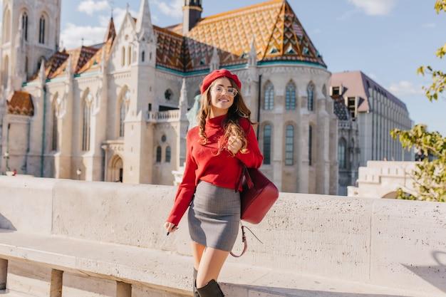 Magnifica ragazza magra in abbigliamento alla moda in piedi davanti al bellissimo palazzo nella soleggiata giornata di settembre