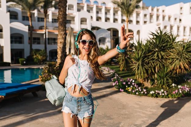 Magnifica ragazza magra con la pelle color bronzo che si guarda alle spalle mentre va dall'hotel alla spiaggia del mare.